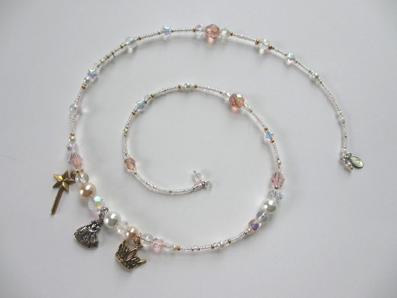 White and pale pink beads represent Glinda's purity and wisdom; tiny glass stars symbolize magic.
