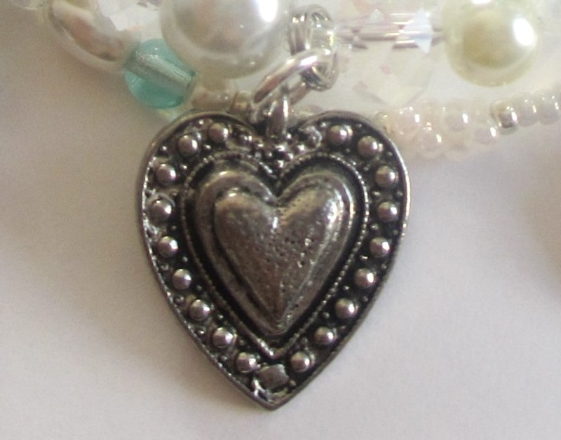 The concentric hearts charm symbolizes love in the many forms presented in the Pearl Fishers.