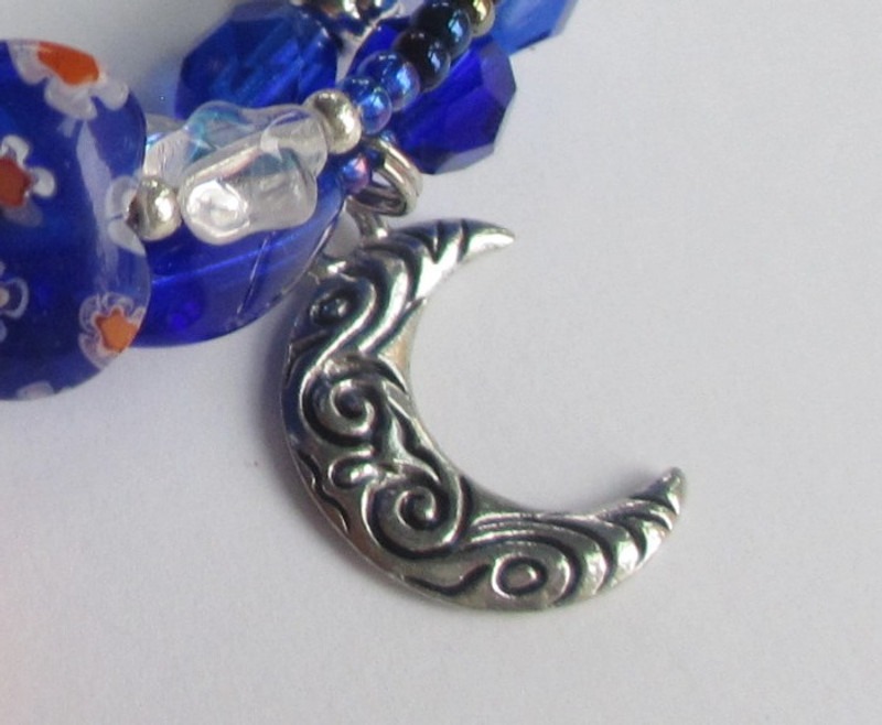 "The moon charm with swirls symbolizes the zephyrs that embrace lovers on the ""beautiful night of love...""."