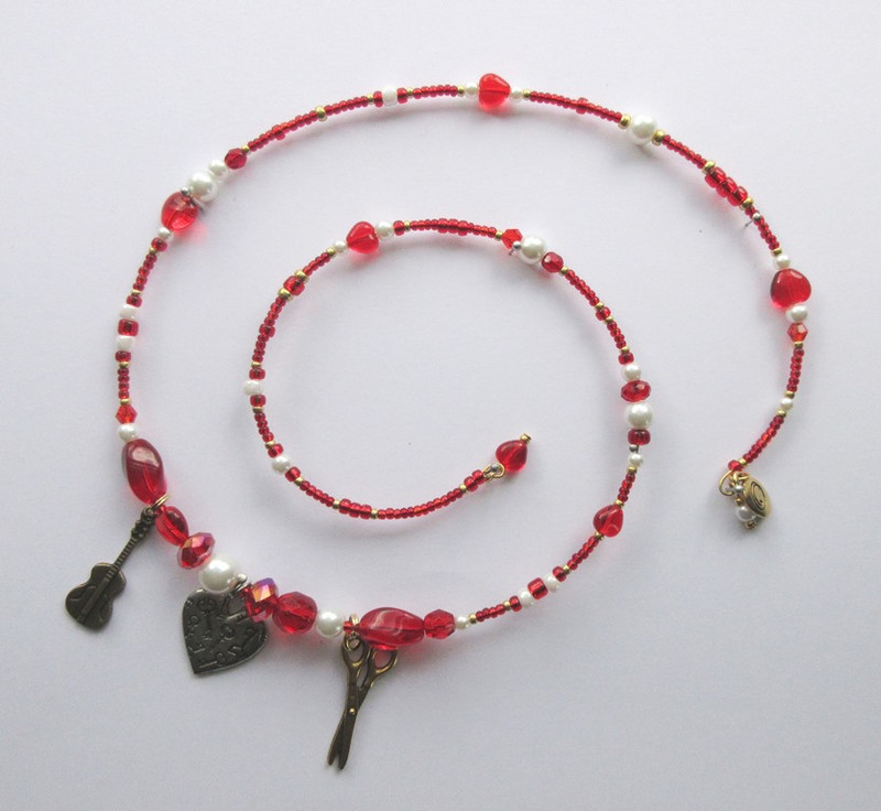 Red and white beads symbolize traditional colors of the barber. Heart beads represent Figaro's role in relationships.