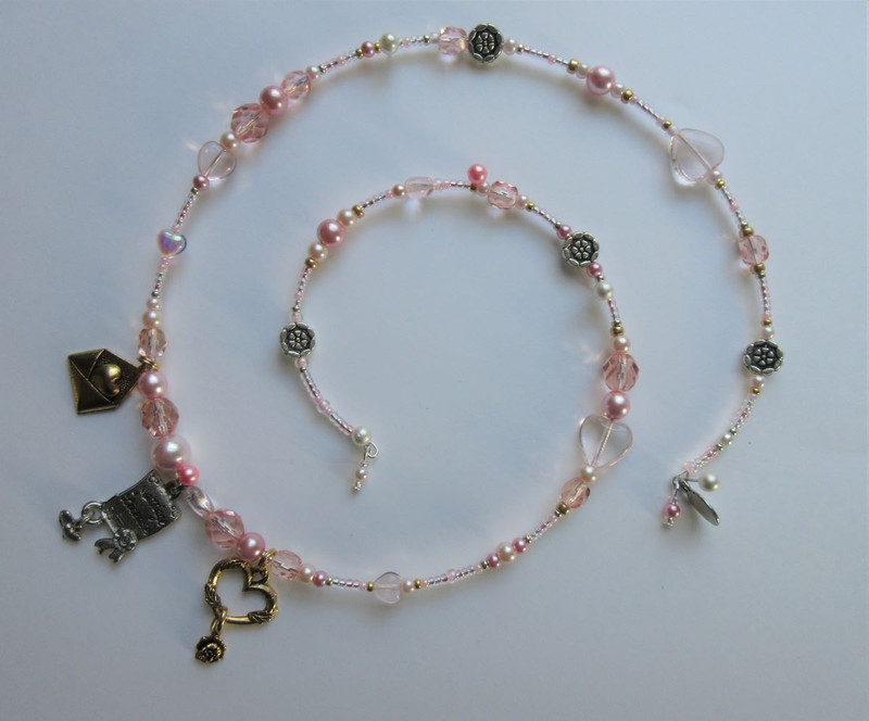 Rose colored beads symbolize the character of Rosina from Rossini's Barber of Seville.