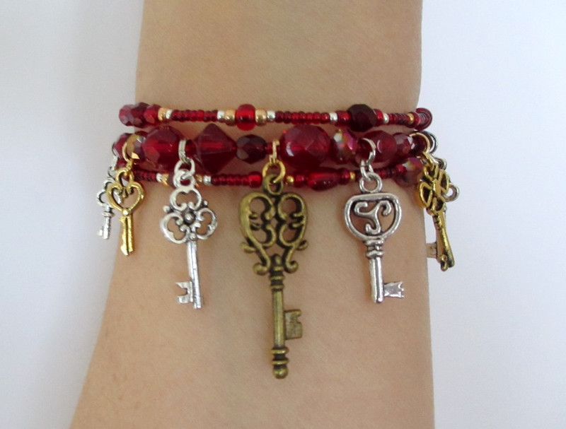 Seven key charms symbolize the seven doors in Bluebeard's Castle. Deep red beads evoke the theme of blood running through the opera.