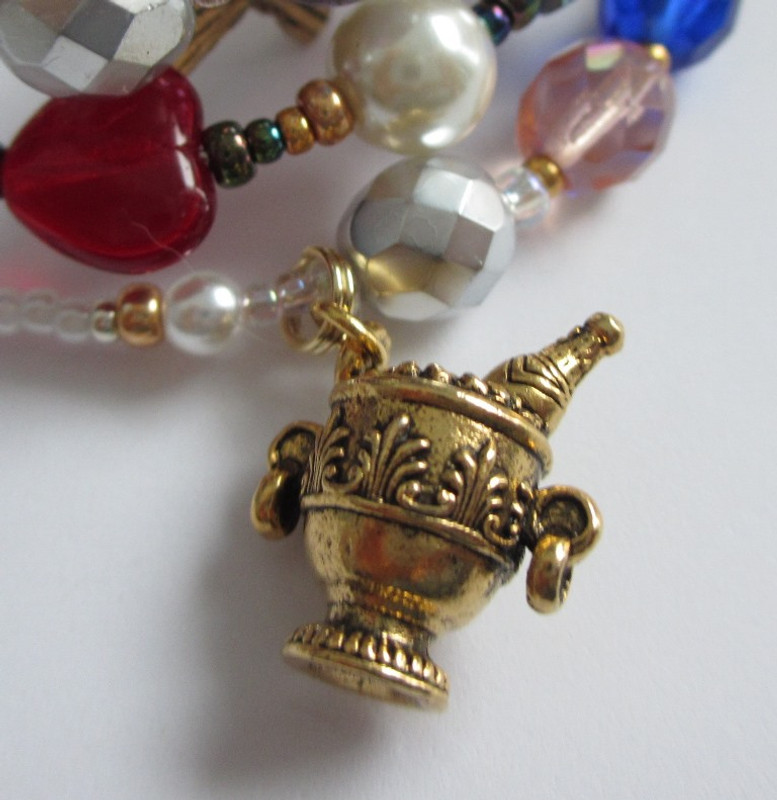 The ornate champagne bucket charm symbolizes the Baron's party at the embassy.