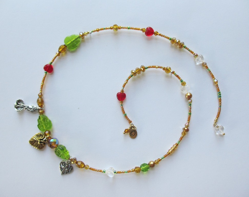 Deep amber beads signify the wood of the Pope's staff. Green leaf beads are the miraculous leaves.