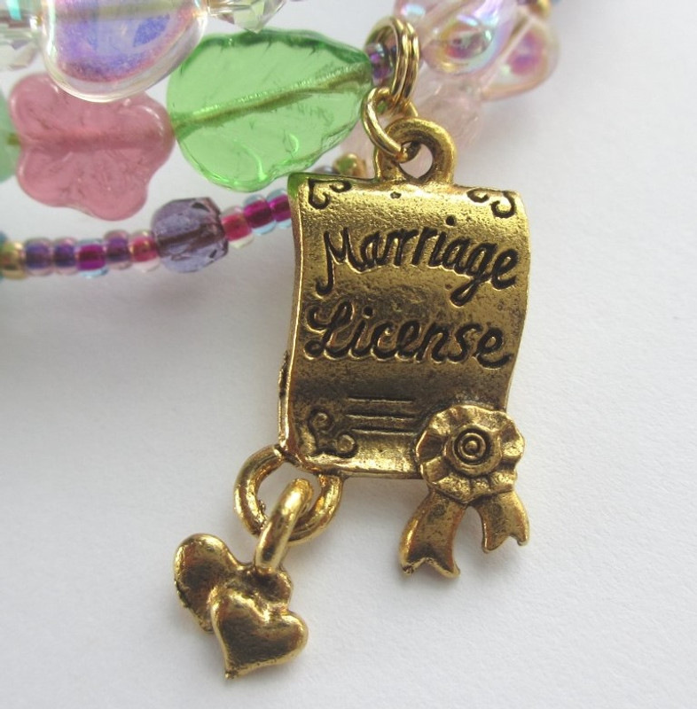 A marriage license charm represents Norina and Ernesto's happy ending together.