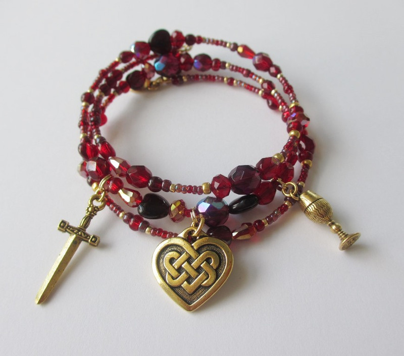 Deep red and wine colored beads with droplets and hearts symbolize the fateful drink.