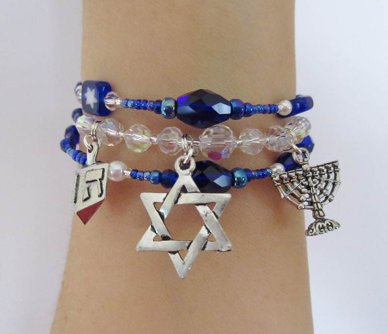Deep blue beads evoke the eight nights of the festival.  Crystals symbolize the flames of the menorah; a larger crystal indicates the special flame of the shamash.