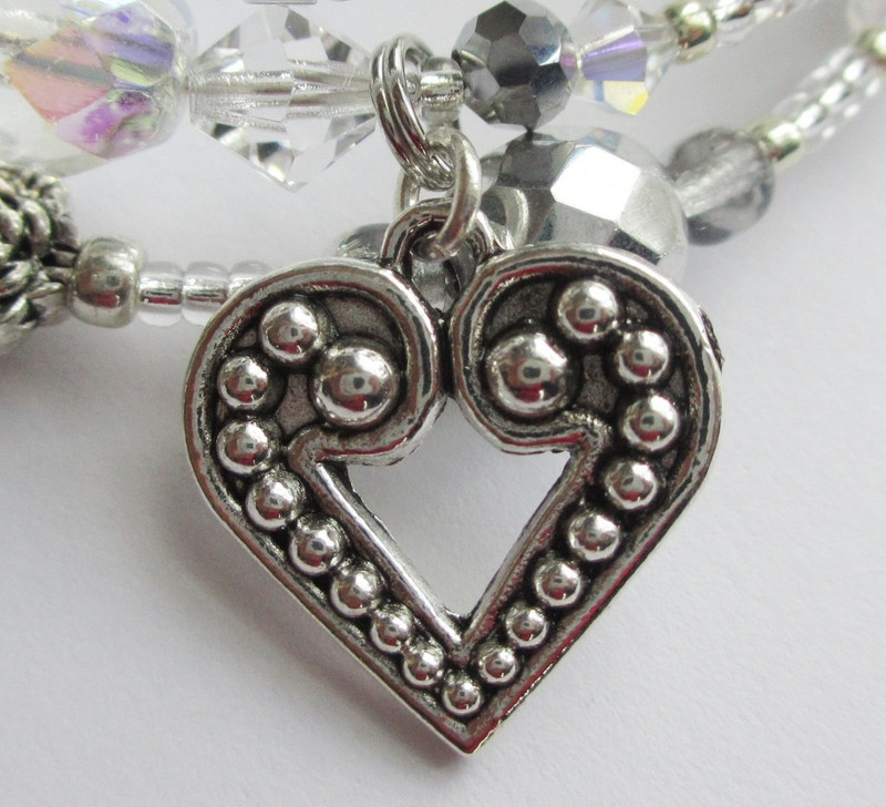 The heart charm symbolizes love as it shifts between the characters in different forms throughout the opera.