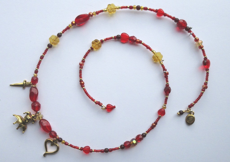 Red beads evoke the red cross of Mantua. Glass hearts are Rigoletto's love for his daughter; golden glass flowers symbolize Gilda.