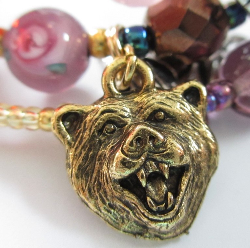 The Beast accuses Belle's father of stealing when  he picks her a rose (rose bead on left).