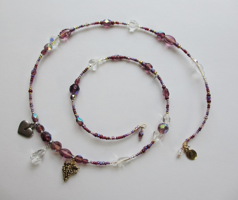 Glass beads in the colors of wine and a bunch of grapes charm indicate the true nature of the love elixir: Bordeaux.