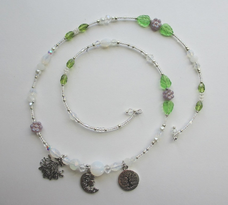 I chose opalescent beads to evoke the silvery moonlight. Glass flowers and leaves indicate the verbena flowers Norma is described as wearing. Tiny pearls with green beads indicate mistletoe.