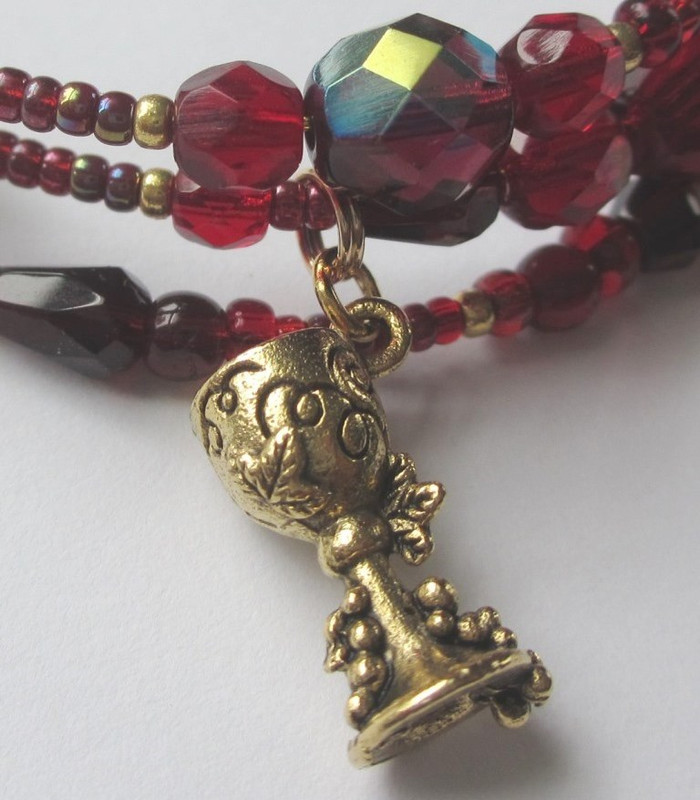 Dagger and wine goblet charms symbolize Turiddu's doom.
