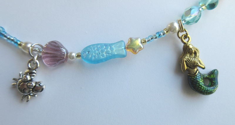 "Shell, fish and ""starfish"" beads with a crab charm evoke the ocean."