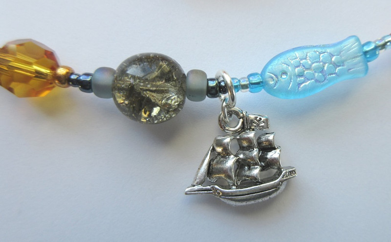 A charm represents the prince's ship. A grey crackle glass bead symbolizes the storm which destroys it and a fish bead symbolizes the ocean.