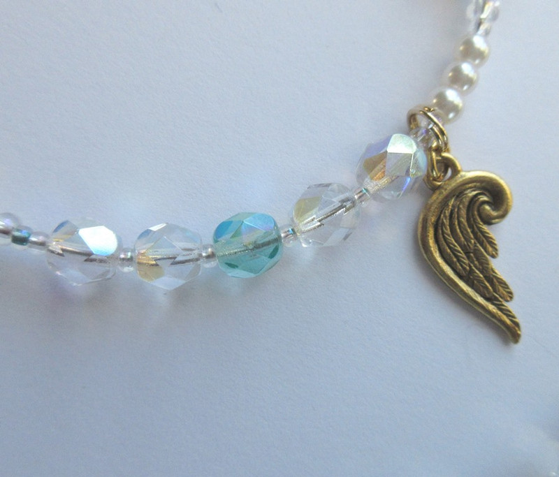 The daughters of air (clear beads with wing charm) save the mermaid's life (aqua bead), and make her one of them.