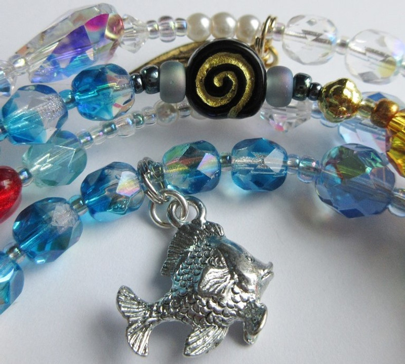 A friendly fish symbolizes the mermaids youth playing with the fishes.  a Dark spiral bead represents the sea witch.