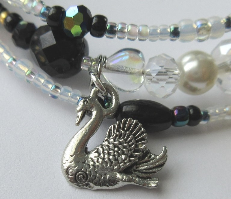 A swan charm represents the curse laid upon Odette.