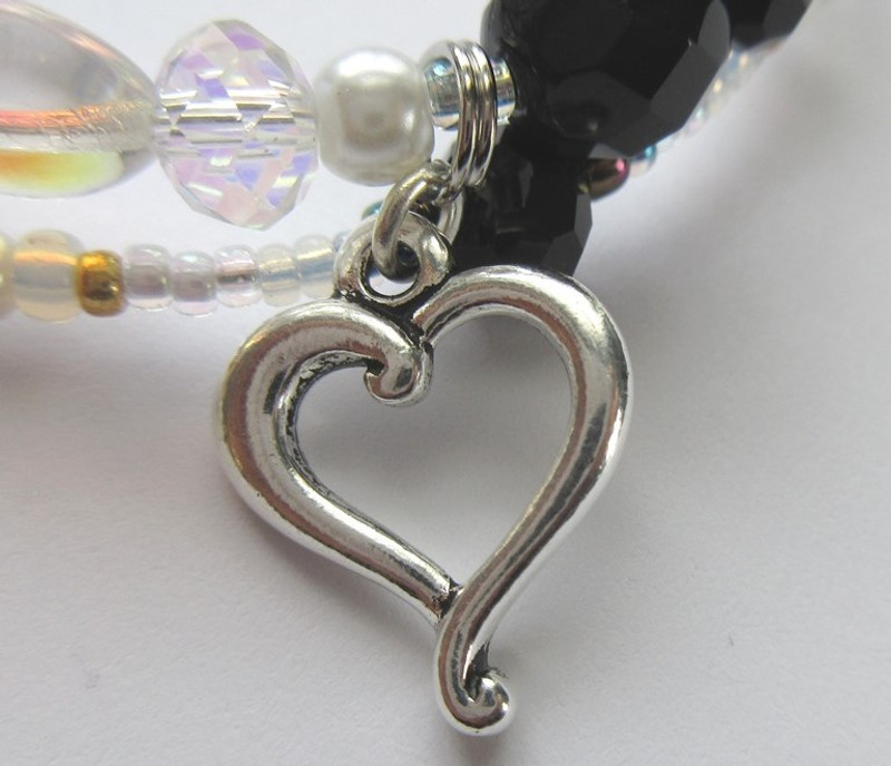 A wavy heart charm evoke the themes of love and redemption.