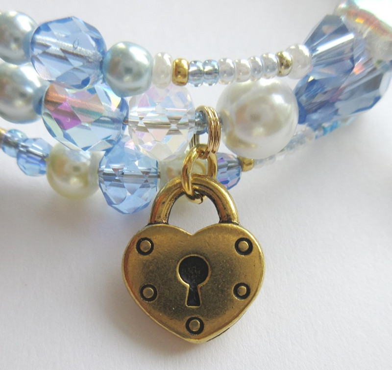 A heart shaped padlock charm symbolizes Maddalena's sacrifice, joining Chenier in prison and in death.