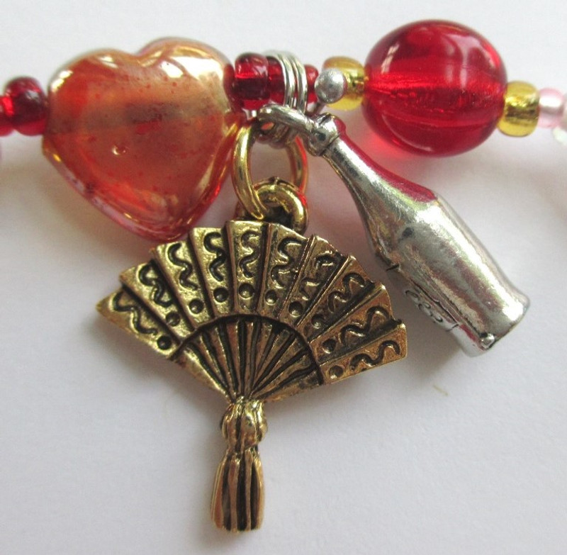The fan and wine bottle charm represent the aria known as Seguidilla.