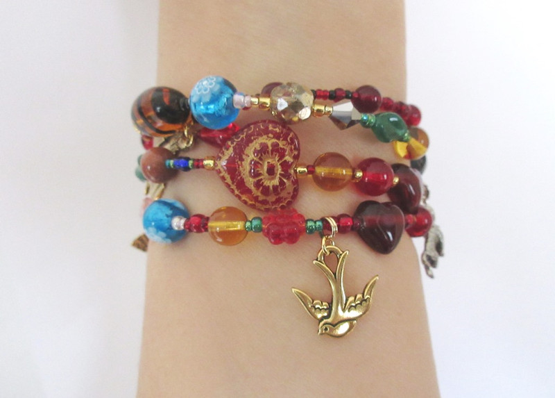 The bird charm framed by a flower and heart bead (bottom of bracelet) symbolizes the words of The Habanera.
