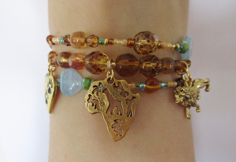 This bracelet is inspired by the beloved tale of Africa, the regal lions of the savannah and the cycle of life, love and renewal.  Beads represent the colors of the savannah: the grasses, bright open skies and the lions. A charm represents the setting of Africa, a lion charm is the majestic animals and a heart with paws represents themes of love and life.