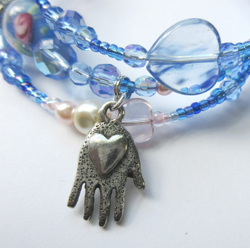 The heart in hand charm evoke her role as a guide, bringing Jose home to see his mother before she dies.