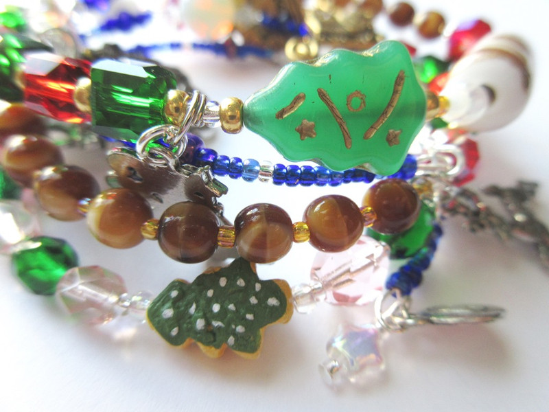 "A cookie bead symbolizes ""sugarplums"", A glass Christmas tree enhances the story bracelet"