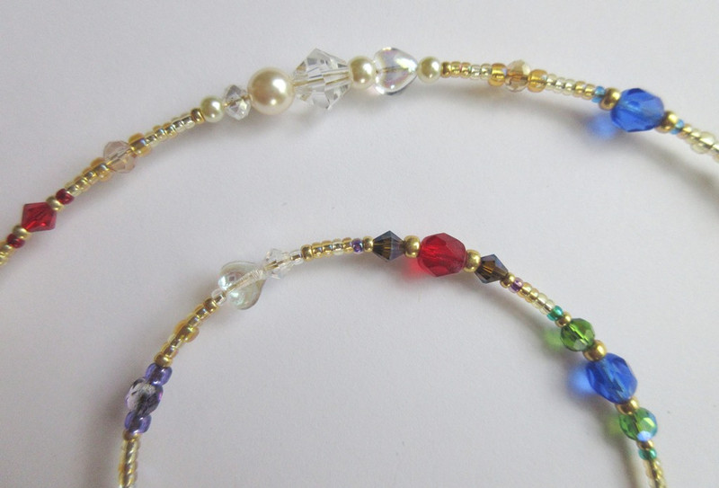 Gold beads with sparkling crystals and pearls represent the riches Manon cannot do without. Beads and crystals in jewel tones indicate gems while glass hearts symbolize love
