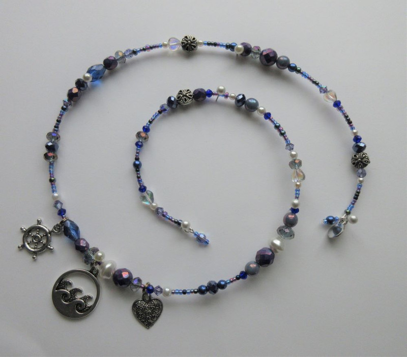 Deep blue and purplescent beads evoke sunlight on the ocean after a storm. Glass pearls and pewter sand dollars further the sea theme