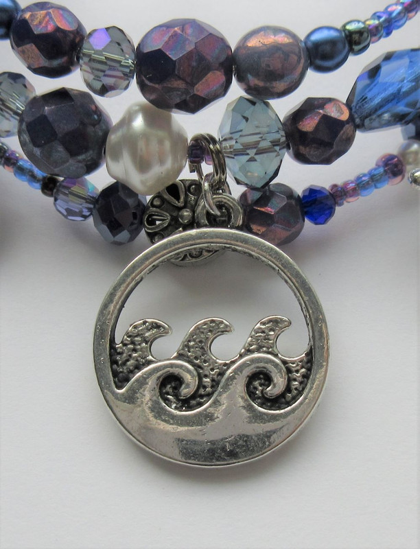 A wave charm indicates the uniting of Senta and the Dutchman through her leaping into the swirling sea.