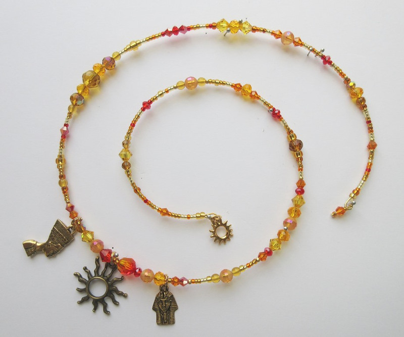 Golden and orange beads with a sun charm represent the god Aten.