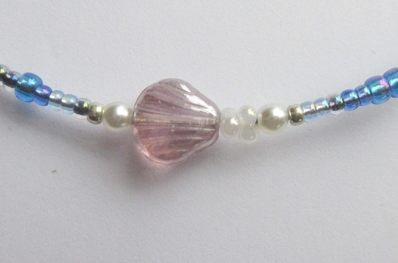 A glass seashell bead with glass pearl accents represents the shore/land.