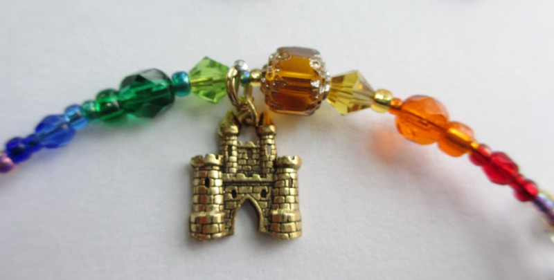 Rainbow colored beads and crystals evoke the rainbow bridge with a castle charm to indicate Valhalla.