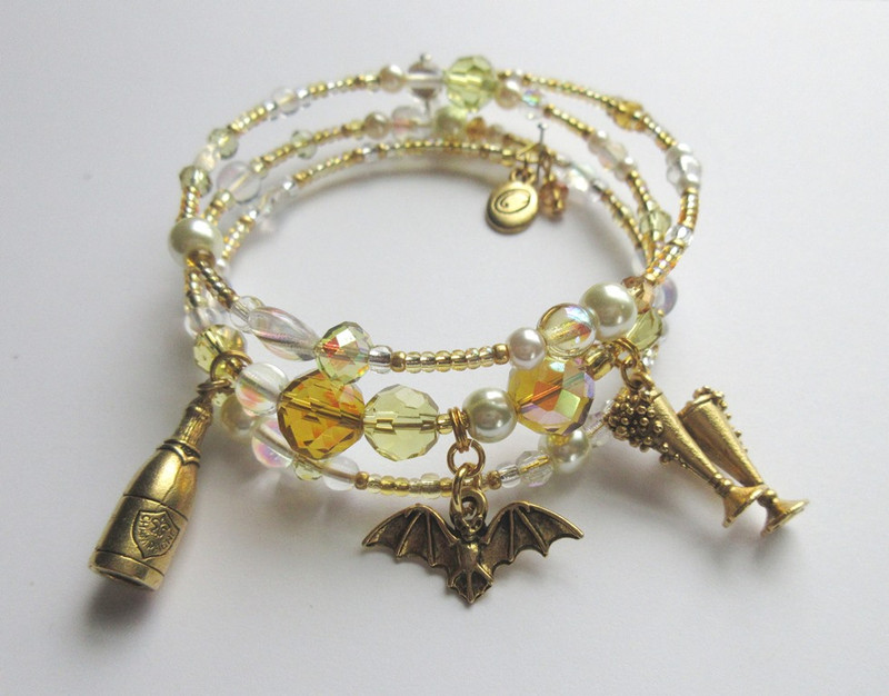 Inspired by Strauss's exuberant opera Die Fledermaus, the Bat and Bubbly Bracelet features bat, champagne glass and champagne bottle charms.