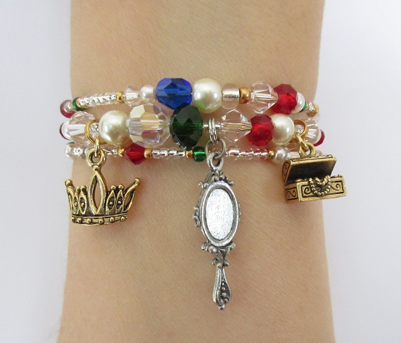 Charms on the bracelet feature the jewel box and the mirror in which Marguerite views herself as a princess (crown).