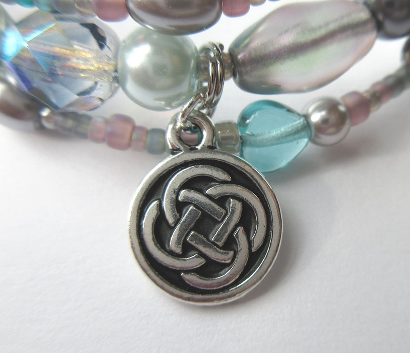 Soft matte finished beads the colors of mist, heather and highlands evoke the Scottish setting. Celtic knots represent eternity.