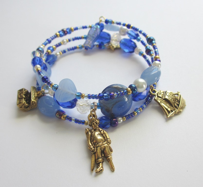 Charms include a Pirate, a pirate ship and a treasure chest. A whimsical fish bead completes the bracelet.