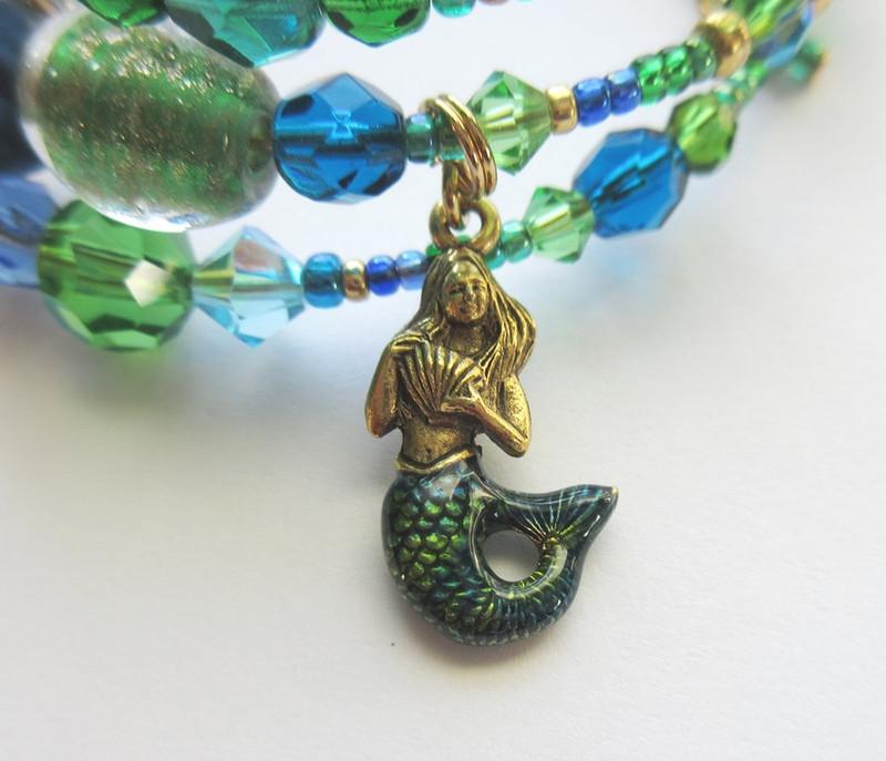 A mermaid charm represents the Rhinemaidens who guard the Rheingold.