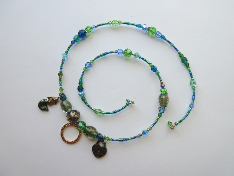 Beads of blue, green, teal and aqua bring to mind the magical Rhine River, further evoked by crystals in watery colors.