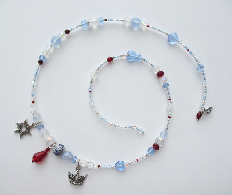 Frosty blue and white beads symbolize the Ice Princess. Touches of deep red evoke the fate of those answer incorrectly.
