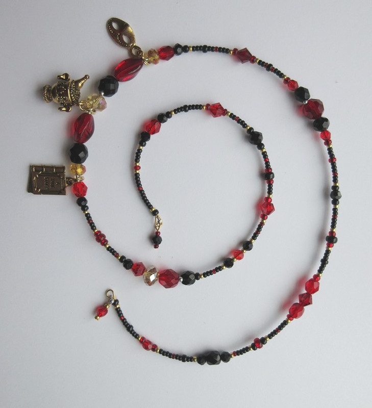 Red beads indicate passion and seduction; black beads are Giovanni's dark fate.