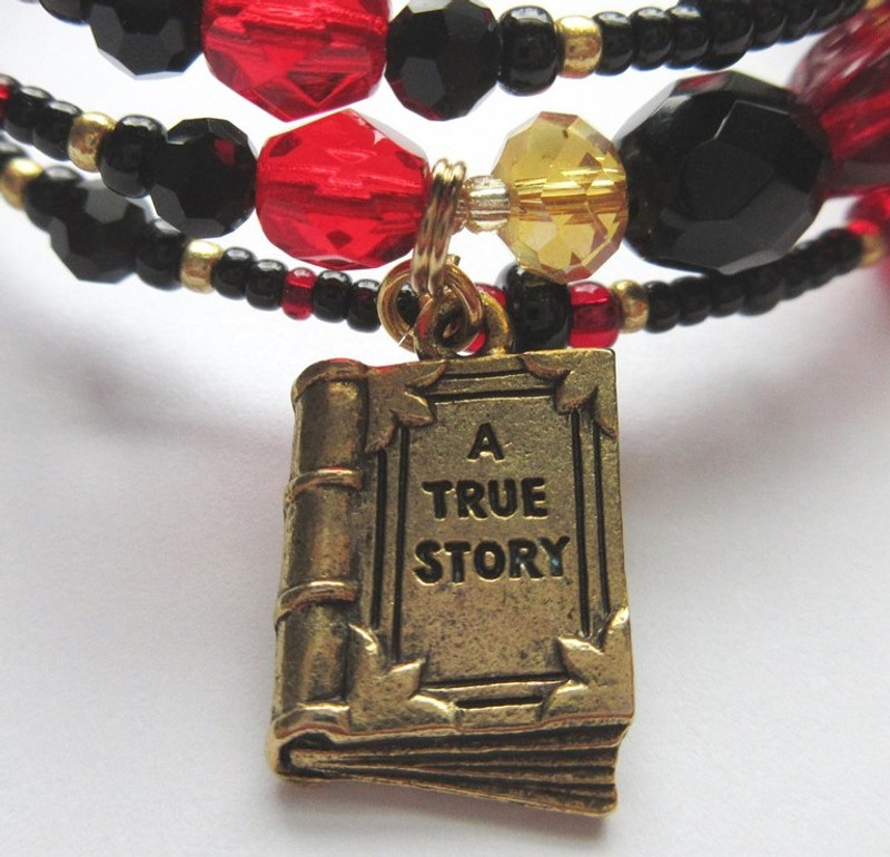 """The book charm symbolizes the Catalogue Aria,  """"Madamina, il catalogo è questo""""."""