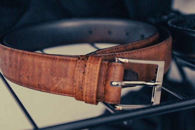 A brown leather belt with a frame-style buckle