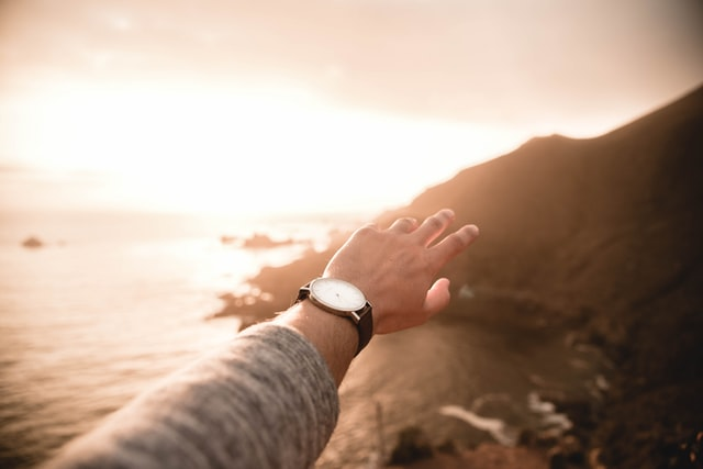 A person's extended wrist wearing a watch overlooking the ocean