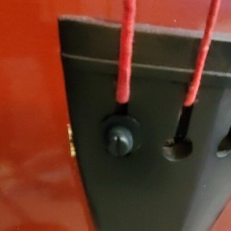 "Plastic hardware for attaching a 1/4"" inline output jack to an upright bass tailpiece - front view, installed on tailpiece"