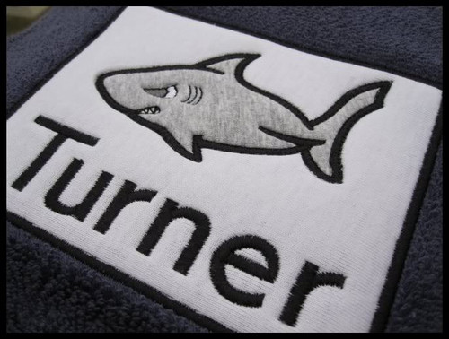 Picture of Applique Shark layered on a rectangle applique frame, stitched on a beach towel - Font is not included in this set.