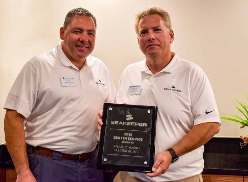 atlant marine owners aaron and charlie holding a plaque