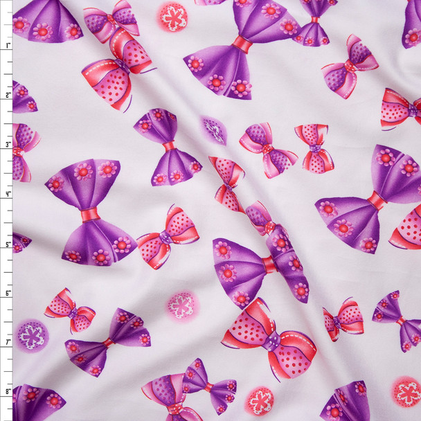 Pink and Purple Tossed Bows on Warm White Brushed Poly Spandex Fabric By The Yard